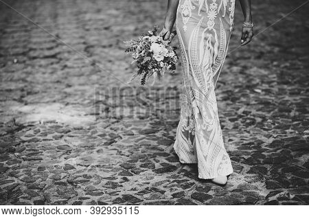 The Brides Hand Holds From Below A Wedding Bouquet, A Look At The Bottom Of The Dress And Womens Fee