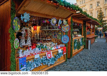 VIENNA, AUSTRIA - DECEMBER 04, 2019: Wooden kiosks on cobblestone street selling gifts and souvenirs during famous traditional Christmas market taking place in old city of Vienna, Austria.