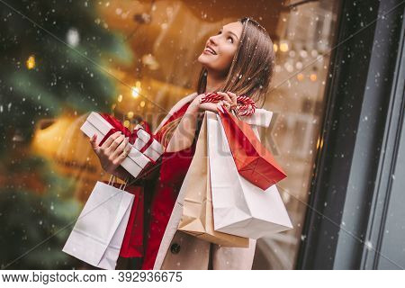 Cheerful Beautiful Young Woman With Paper Bags And Present Boxes After Christmas Shopping In Mall. A