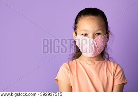 New Normal. Portrait Of Little Asian Child Wearing Reusable And Washable Protective Face Mask Made O