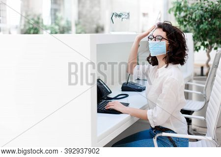 Receptionist Wearing Protective Mask At Reception In Hotel. Protection Employees On Workplace. Young