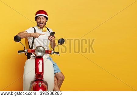Isolated Shot Of Happy Delivery Man Points At Smartphone Used For Finding Route Or Right Address, Co