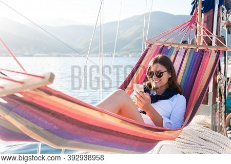 Woman Relaxing On Yacht In Beach Hammock. Traveler With Mobile Phone. Travel On Sailboat. Enjoying S