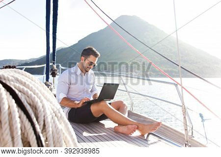 Man Working On Yacht Office With Laptop. Traveling On Sailboat. Traveler Using Tablet Computer. Free