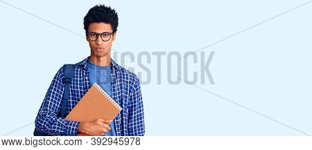 Young african american man wearing student backpack holding book skeptic and nervous, frowning upset because of problem. negative person.