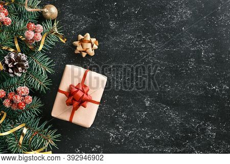 Christmas And New Year Festive Background With A Gift Box, Fir Tree Branches And Seasonal Decoration