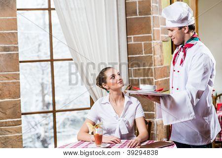 Chef brings a dish pretty woman in a restaurant