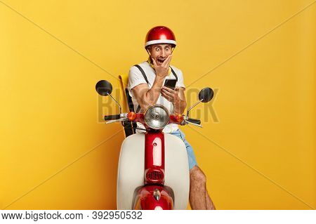 Horrified Male Motorcyclist Stares At Modern Mobile Phone, Cannot Believe In Shocking News, Wears He