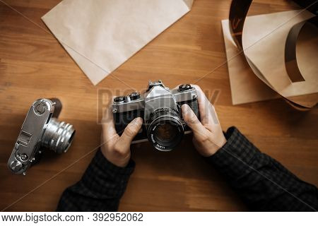 Top View On Hands Holding Retro Film Pentax Camera On The Wooden Table