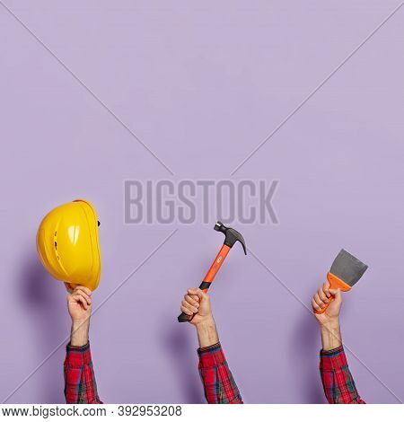 Human Hands With Yellow Hardhat, Hammer And Brush For House Repair. Collection Of Various Equipment