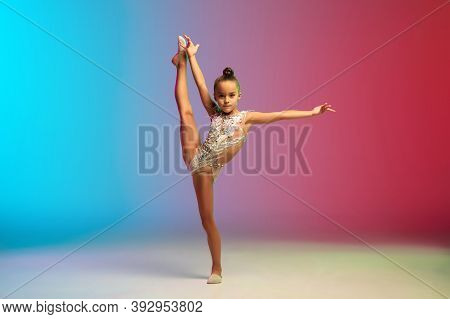Dynamic. Little Caucasian Girl, Rhytmic Gymnast Training, Performing Isolated On Gradient Blue-red S