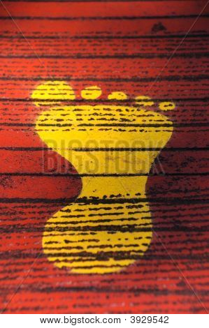 Yellow Footprint Against Red Background