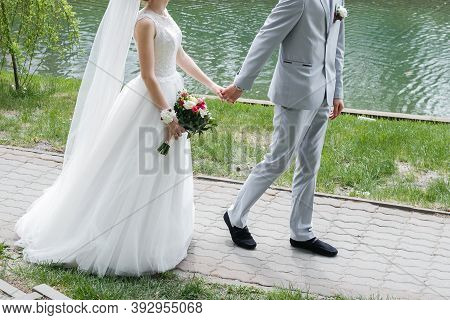 Close Up Of Stylish Newly Married Couple Walking Together In The Park On A Background Of Lake On The
