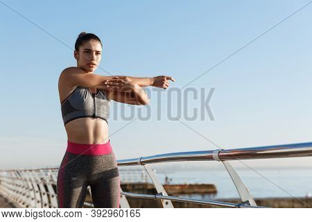 Young Serious Female Athlete In Sportswear Stretching Her Body Before Jogging Workout. Sportswoman S