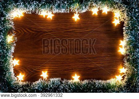 Christmas Lights On Wooded Background. Christmas Background, A Table Decorated With Christmas Garlan