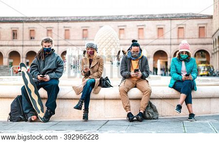 Millenial Friends Watching Video On Smart Phones With Face Mask On Covid Second Wave - Worried Guys