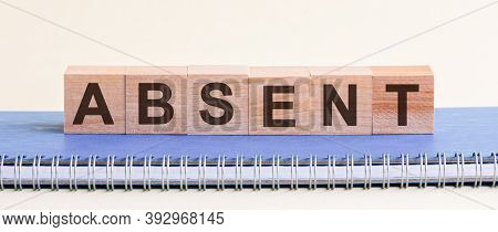 Absent - A Word Made Of Wooden Blocks With Black Letters, A Row Of Blocks Is Located On A Blue Notep