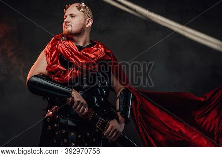 Handsome And Hairless Roman Guardian With Red Cloak And Black Armour Poses With Sheathed Sword In Da