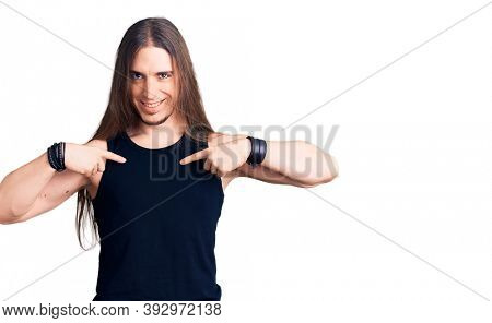 Young adult man with long hair wearing goth style with black clothes looking confident with smile on face, pointing oneself with fingers proud and happy.