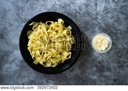 Take Away Pappardelle Pasta With Grated Parmesan Cheese In Plate Ready To Serve And Eat In Black Pla