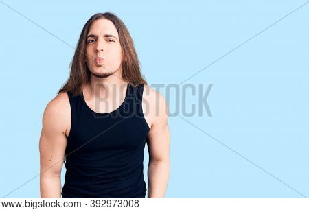 Young adult man with long hair wearing goth style with black clothes looking at the camera blowing a kiss on air being lovely and sexy. love expression.