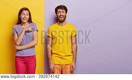 Funny Smiling Woman Points At Dejected Guy With Sorrowful Expression, Faces Problem, Stands Over Col