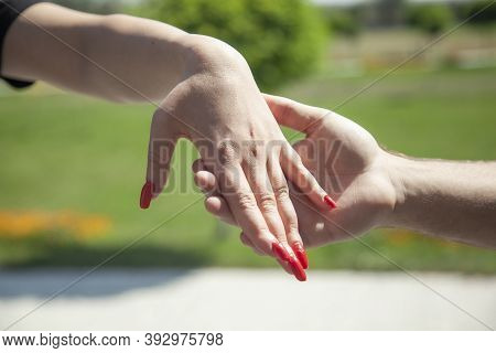 Close Up On A Couple Holding Hands In The Park