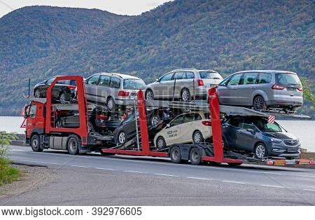 An Automotive Car Carrier Truck Driving Down The Highway With A Full Load Of New Vehicles. Big Car C