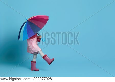 Happy Little Child Girl With Multicolored Umbrella In Pink Rain Coat And Rubber Boots On Blue Backgr