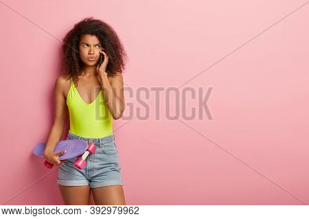 Sporty Dark Skinned Female Has Extreme Hobby, Holds Purple Longboard, Has Unpleasant Phone Conversat