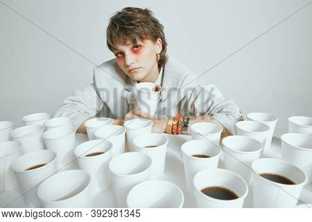 Weary Female And Lots Paper Cups For Coffee On Gray Studio Background