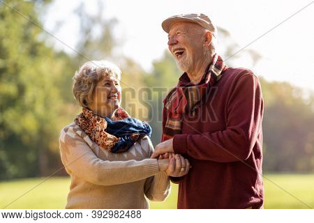 Happy senior couple spending time together in beautiful city park in autumn