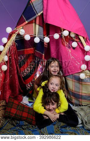 Kids Embrace In Home-made Tent Inside The Living Room Before Going To Sleep. Child Pajama Party. Paj