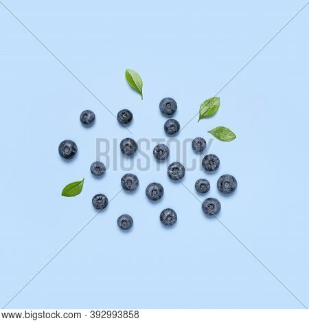 Fresh Juicy Blueberries With Green Leaves On Blue Background. Blueberries Background. Flat Lay Top V