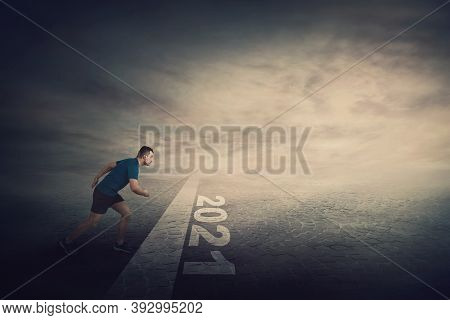 Determined Man Stands In Running Position, At The Start Line, Looking Ahead Confident. Guy Sprinter