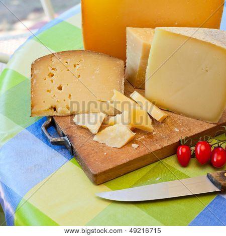 Pecorino sardo cheese slices on wooden board