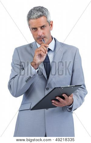 Assiduous businessman on white background holding clipboard and taking notes