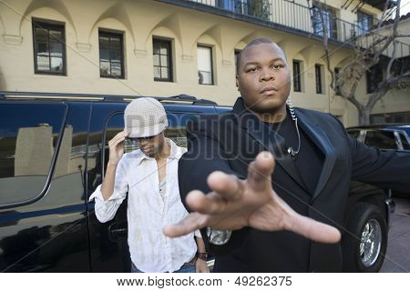 Male celebrity with his bodyguard against a vehicle