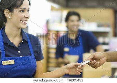 Primer plano de una tarjeta de fidelización empleada dando mano en supermercado