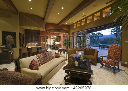 Living room with dining and kitchen area in background at modern home