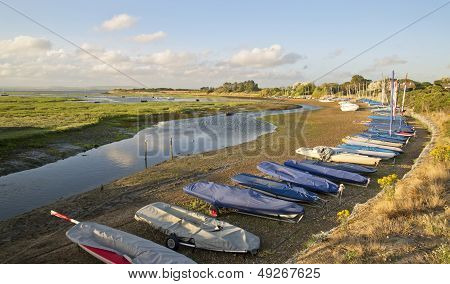 Small Leisure Boats Moored At Low Tide In Marina At Summer Sunset