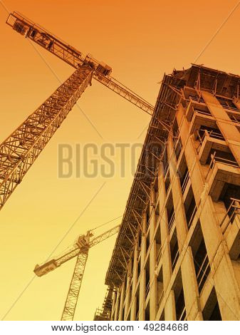 Highrise building under construction and two jib cranes over sunrising sky