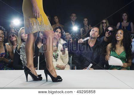 Spectators watching a model walk in black high heeled shoes