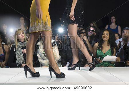 Spectators watching models walk in black high heeled shoes