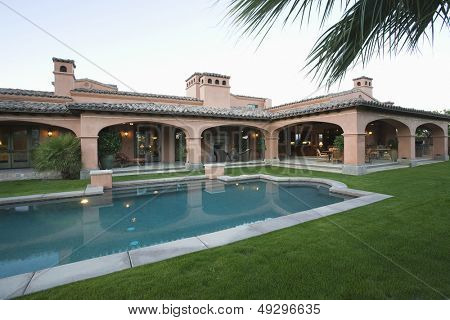 Swimming pool and lawn in front of spacious house against clear sky