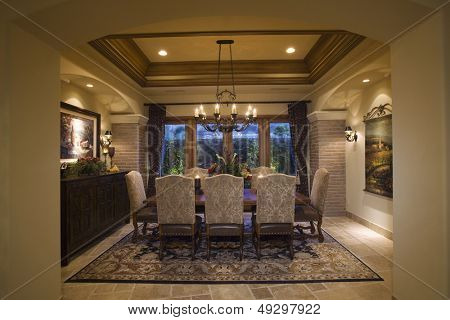 View of lit chandelier over dining table and patterned rug at home