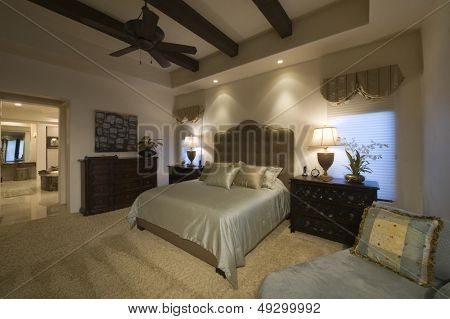 Silk cover on double bed in spacious bedroom with beamed ceiling at home