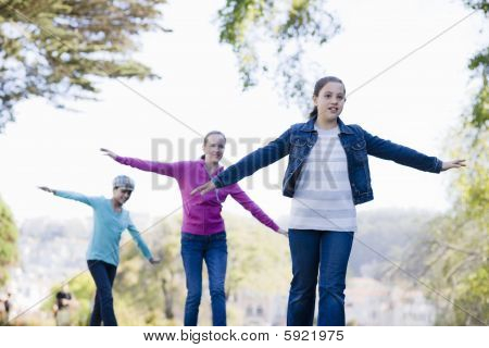 3 Tween Girl Balancing On Wall By Pond