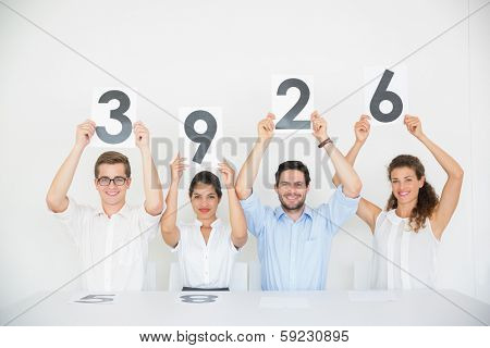 Portrait of panel judges holding score signs in office