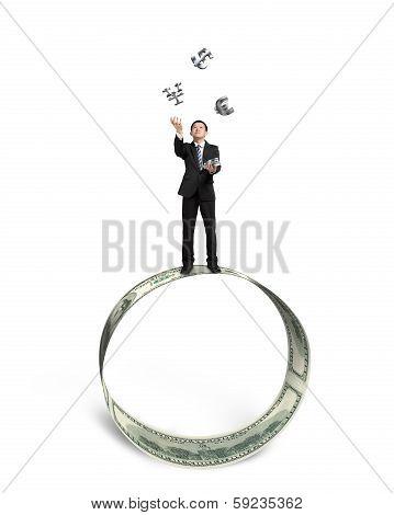 Businessman Catching And Throwing Money Symbols On Money Circle